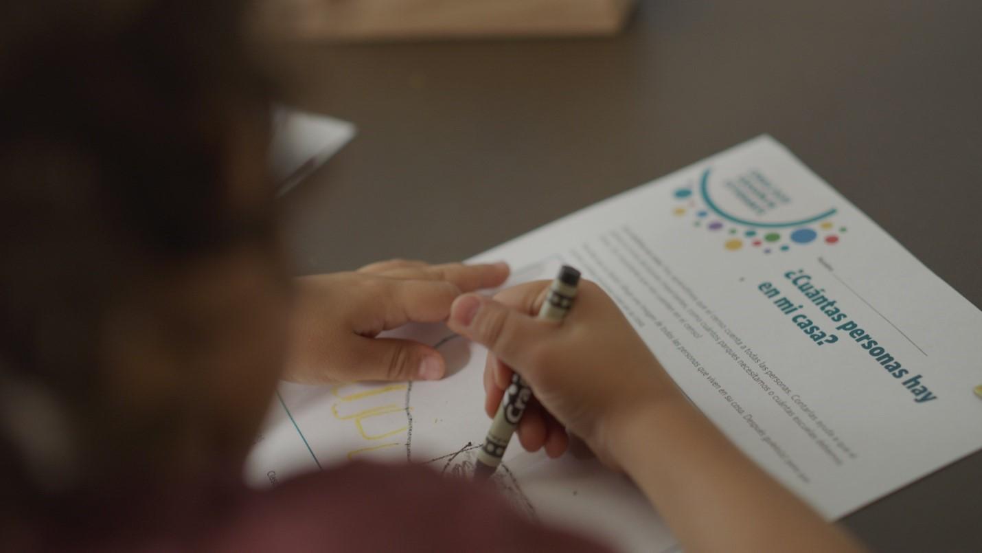 Un niño colorante un página de census por niños.