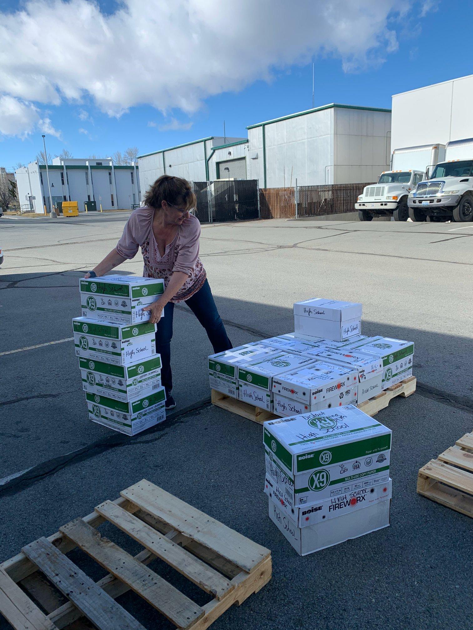 Maestra apilando cajas de papel de copia.