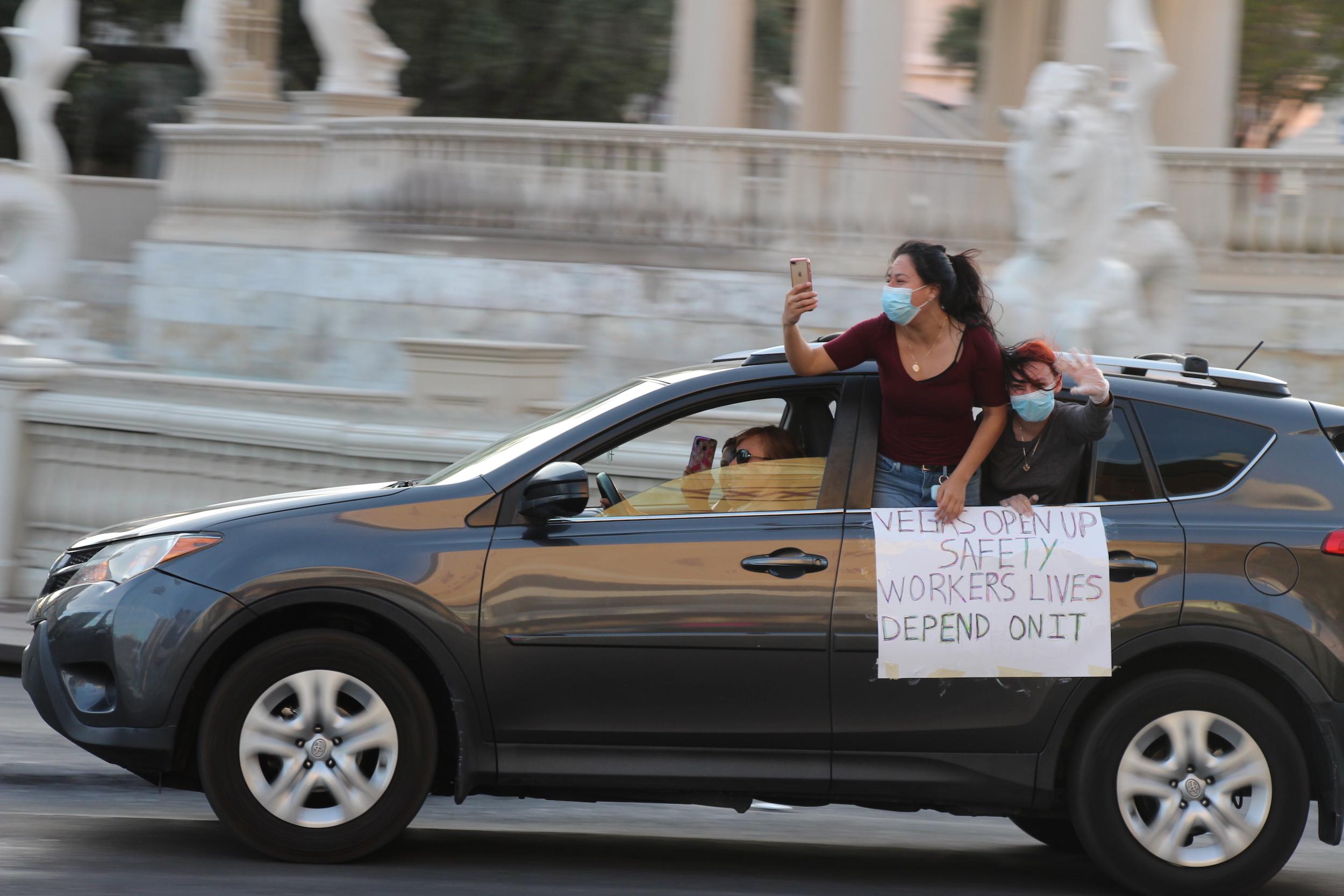 Una mujer saca la cabeza de un auto para llamar atención a la salud de los trabajadores de casinos.