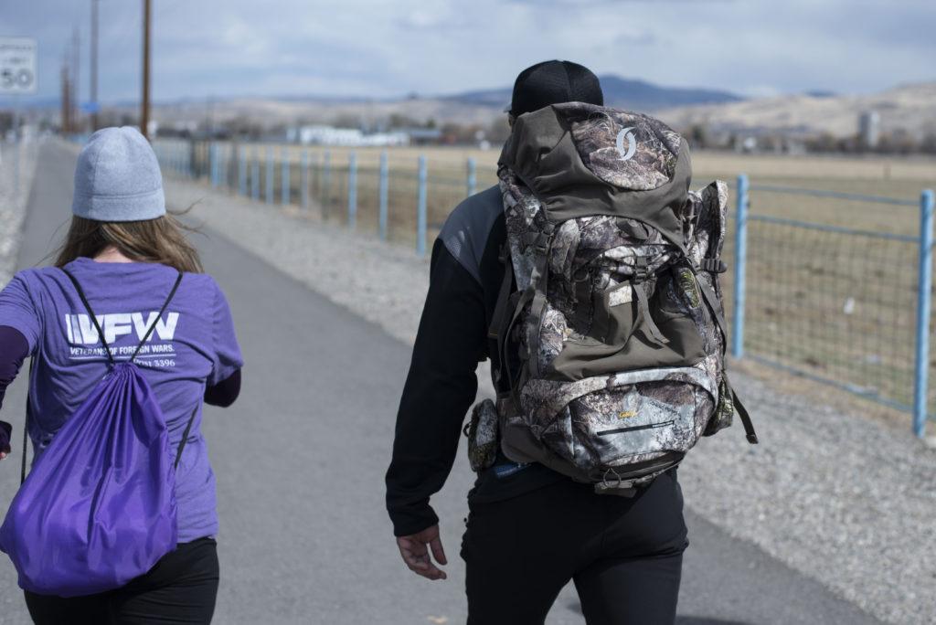 Un hombre y una mujer con mochilas, caminando por un sendero al lado del camino.