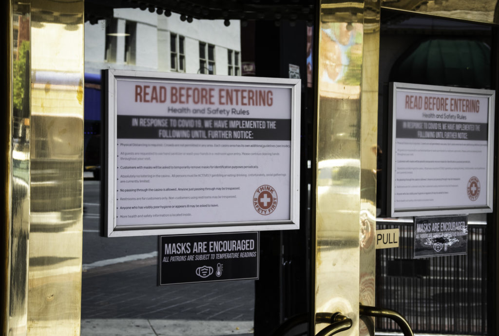 Afiche en puerta del Club Cal-Neva con avisos sobres COVID-19.