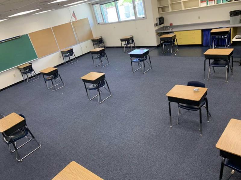 escritorios colocados a distancia en una salón de clases