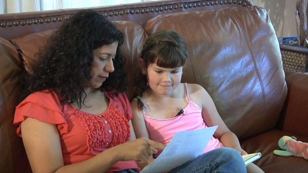 Mujer adulta repasa tarea con niña