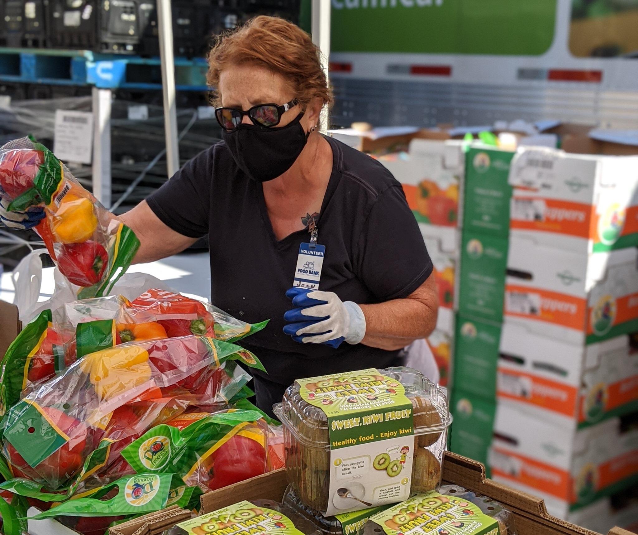 Una mujer desempaca una caja de tomates para una distribución de productos frescos.