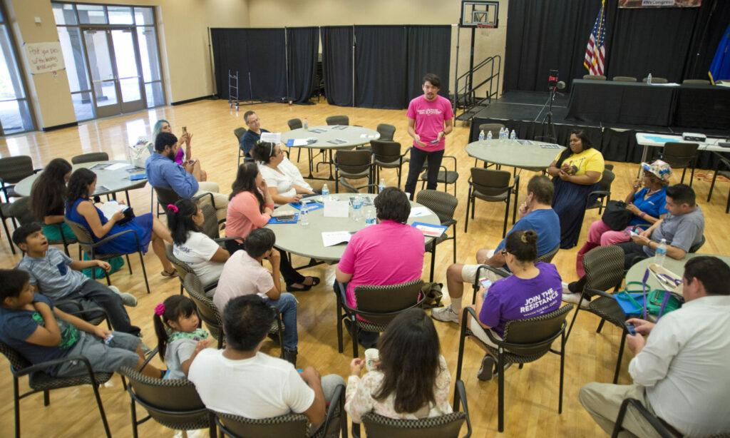 Una docenas de personas sentadas alrededor de mesas redonda hablando juntos