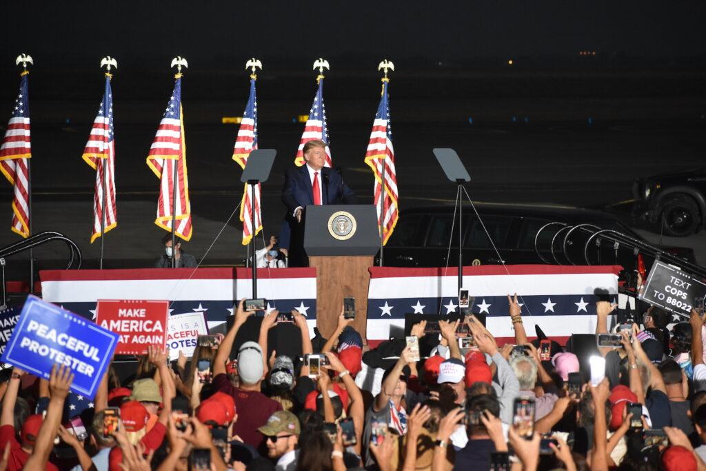 El presidente Donald Trump habla desde un podio. En primer plano, aparece una gran multitud de seguidores con carteles y teléfonos móviles. Varias banderas estadounidenses se muestran detrás de Trump.