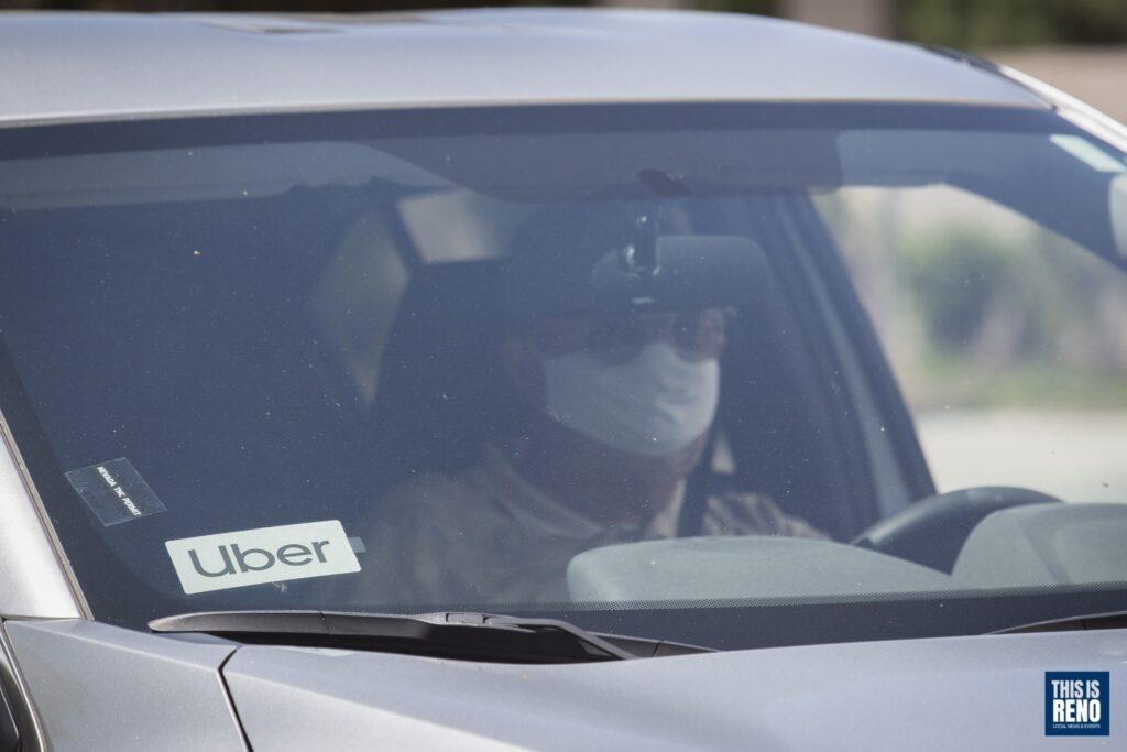 Un conductor de Uber usa una máscara mientras trabaja.