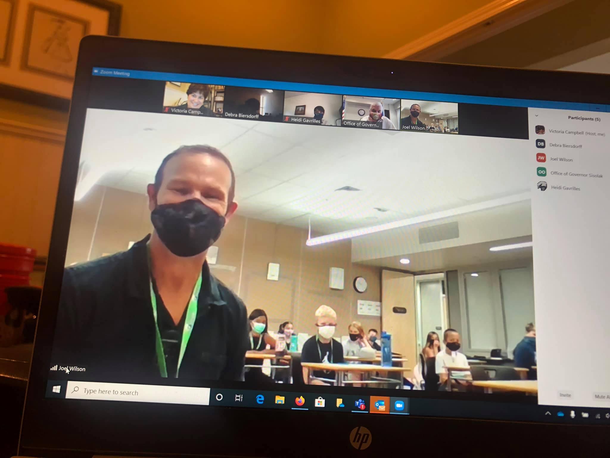 Maestro con máscara se puede ver por pantalla. Detrás tiene una clase de estudiantes también portando tapabocas.