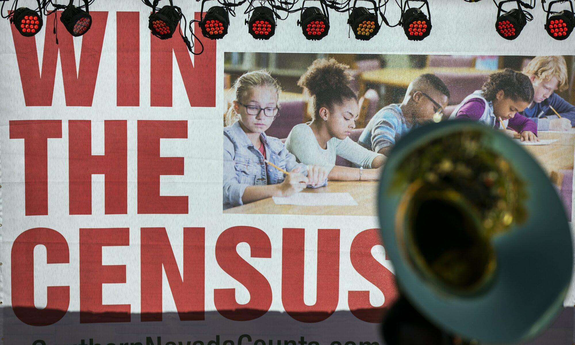 """Foto de otra imagen que dice """"ganar el censo"""" en inglés e incluye niños. Frente a la imagen se puede ver una trompeta."""