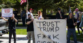 """Dos de unas ochos personas en la imagen aguantan letrero con frase """"Confíen en Trust"""""""
