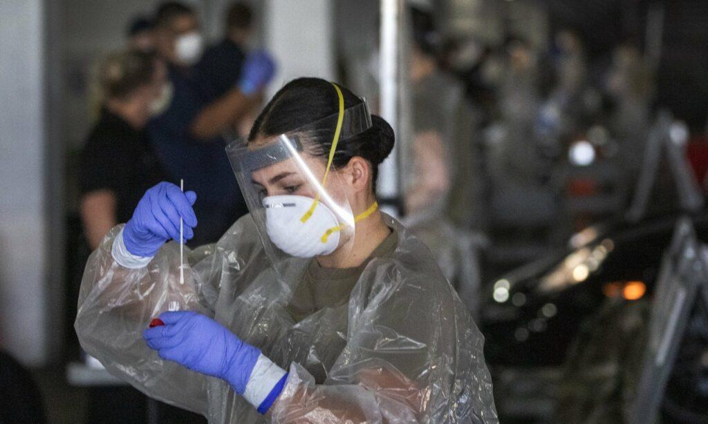 Integrante de la Guardia Nacional de Nevada coloca un hisopo en un recipiente después de realizar una prueba de COVID-19