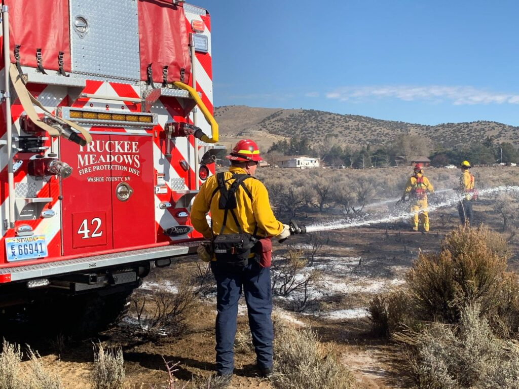Un bombero riega agua sobre el pasto ya quemado.