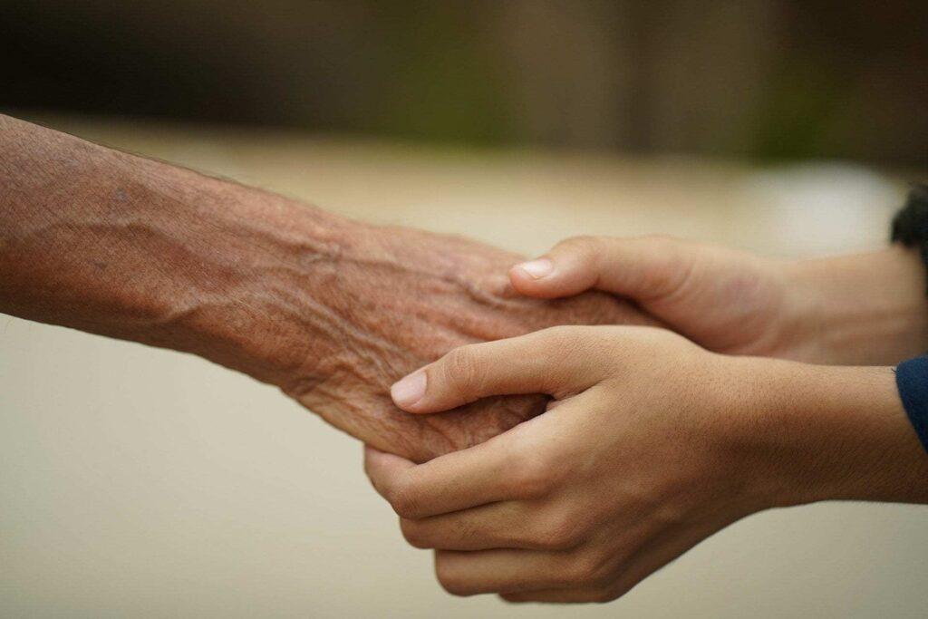 Las manos de una persona joven toman las de una persona de edad avanzada