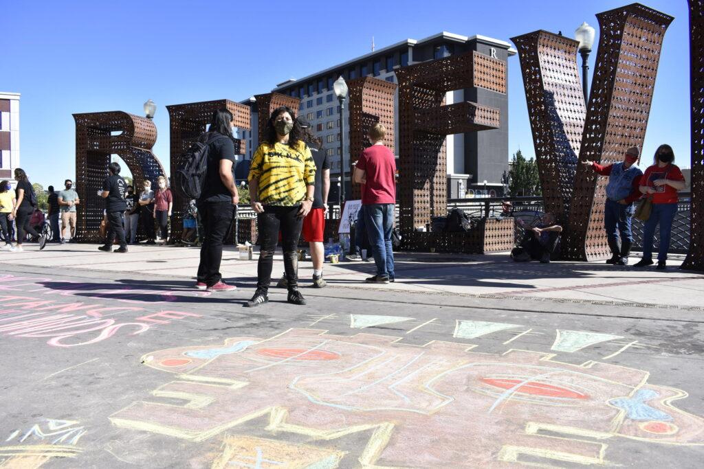 una mujer que viste una camisa amarilla y negra y lleva una máscara, está parada en la esquina. En el suelo, frente a ella, hay un dibujo de tiza que se asemeja a una cara.