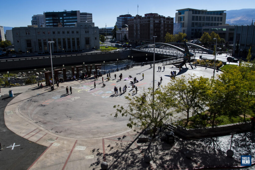 una toma aérea de una plaza muestra a personas que dibujan con tiza en el suelo. Hay árboles al frente y un río y edificios al fondo.