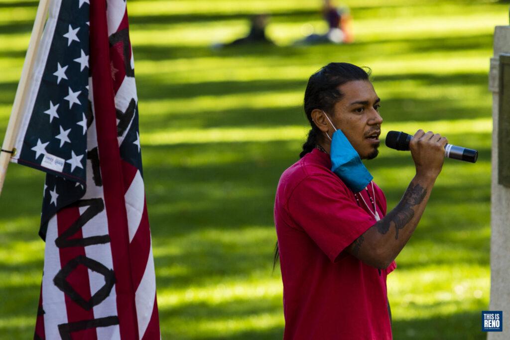 un hombre con una camisa roja y una máscara alrededor de una oreja sostiene un micrófono. Está parado al lado de una bandera estadounidense y hay césped detrás de él.