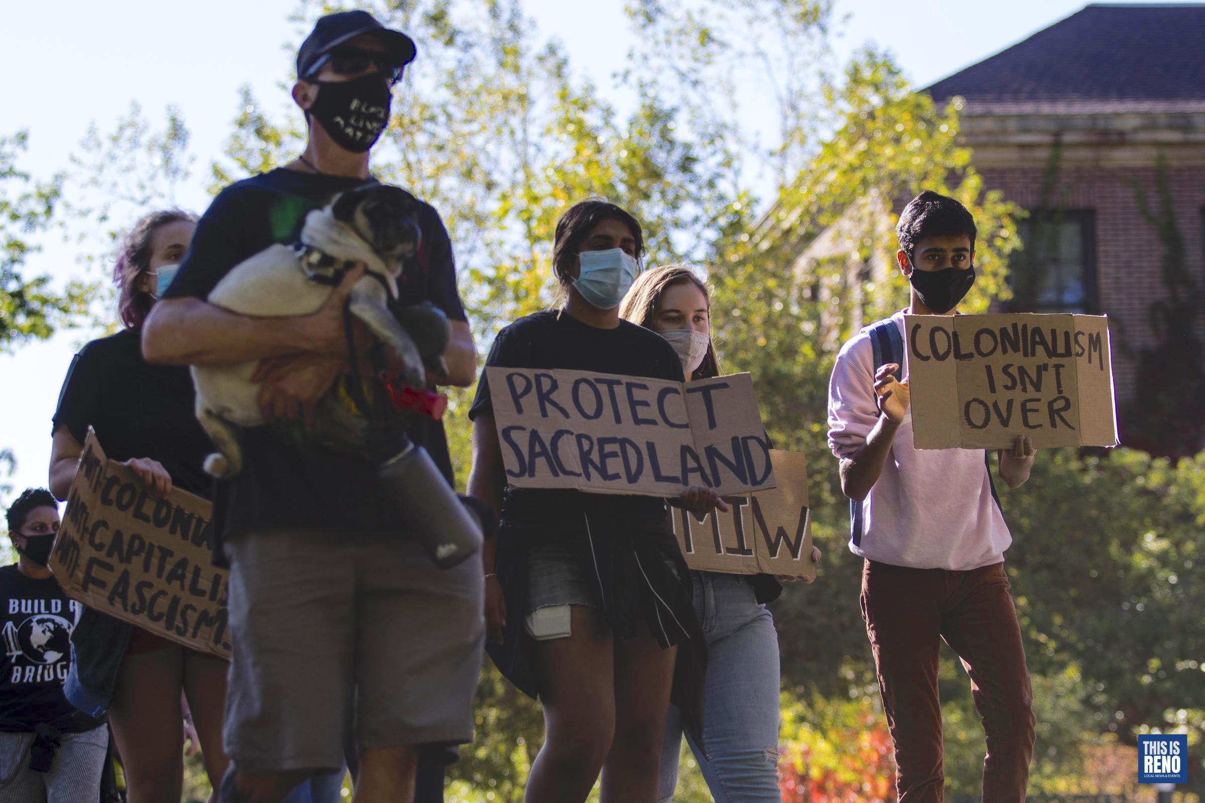 """Un grupo de personas marcha. Una persona sostiene un perro. La gente sostiene carteles en los que se lee: """"Protege la tierra sagrada"""" y """"El colonialismo no ha terminado""""."""