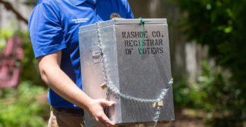 Hombre carga caja on boletas electorales hecha de hiero y cerrada con candado