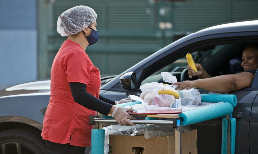 Una mujer recibe una bolsa de alimentos mediante la ventanilla de su carro.