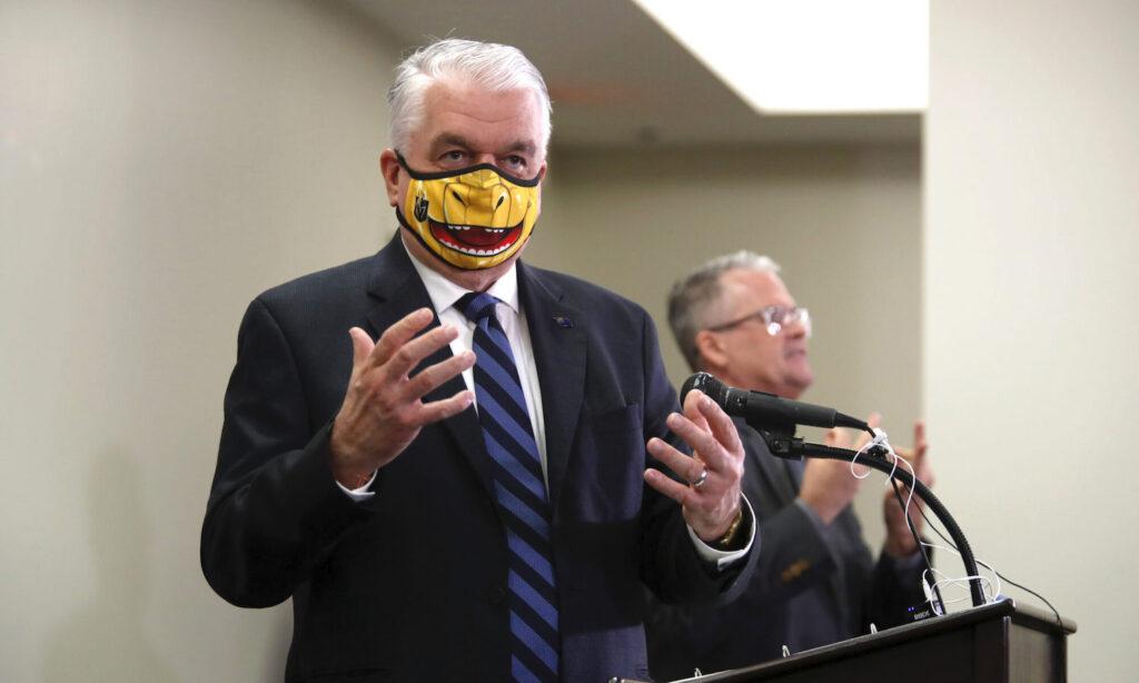 El gobernador de Nevada, Steve Sisolak, responde a una pregunta durante una conferencia de prensa. La mascarilla que porta tiene como tema a Chance the Golden Gila Monster, la mascota del equipo de hockey Vegas Golden Knights.