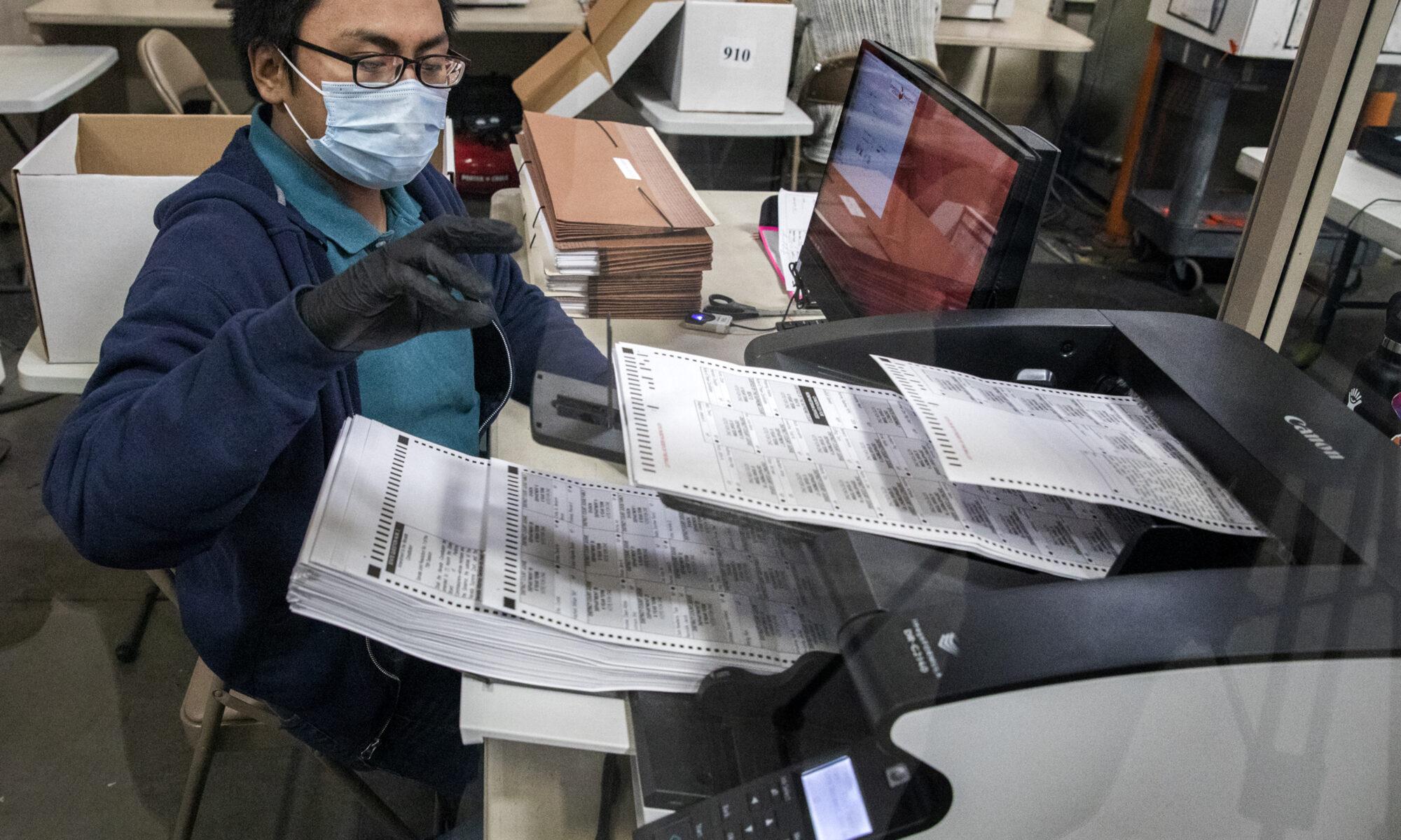 Un hombre con máscara quien transporta boletas pasa frente a observadores