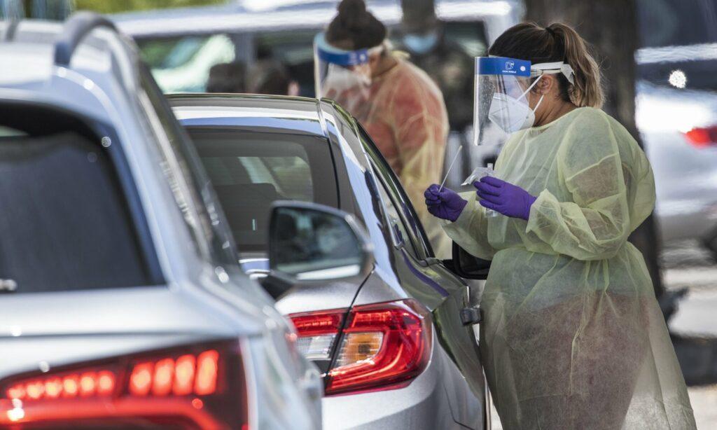 Mujer ofrece prueba de COVID-19 por la ventanilla de un carro