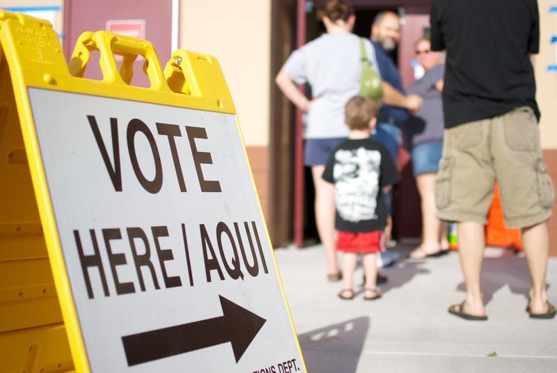 Letrero con Vote Aquí escrito y personas en fila