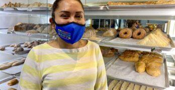 Una miembro de la comunidad está de pie frente al pan dulce. Lleva mascarilla.