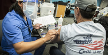 Una enfermera injecta a paciente con vacuna