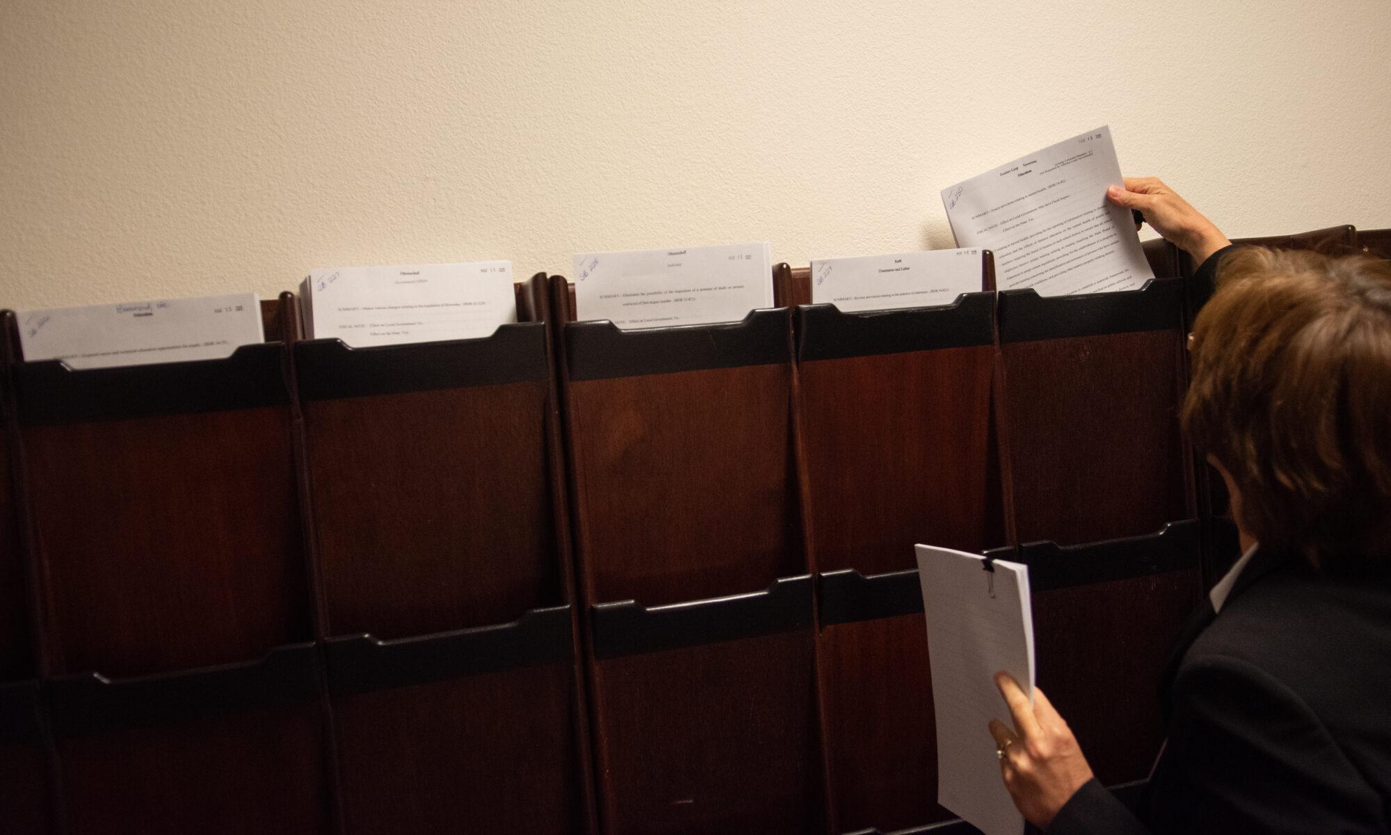 La mano de un hombre colocando papeles en casillas de un mueble café