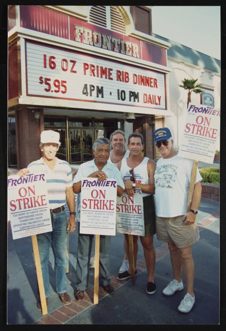 Cinco hombres posan con letreros huelguistas