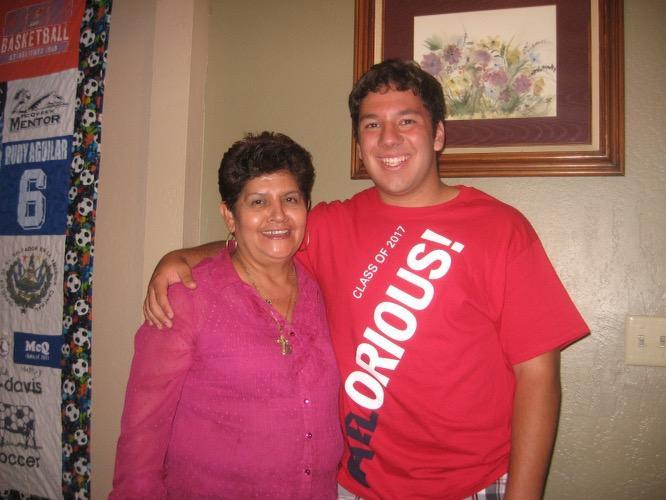 Una mujer en una blusa rosada posa junto a su sobrino en una polera roja