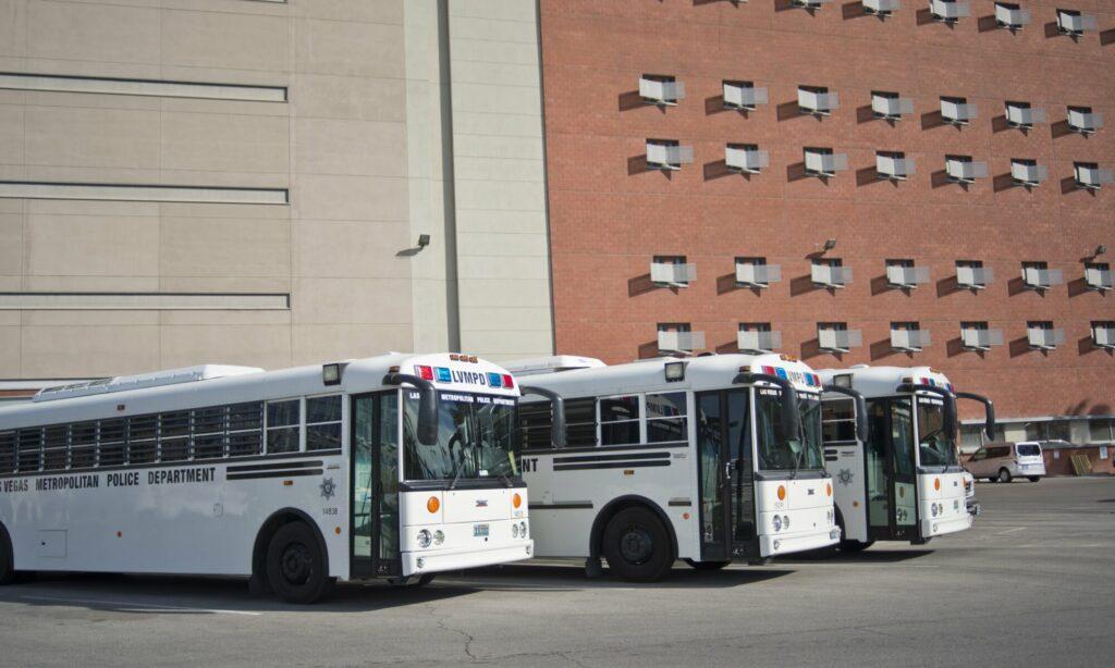 tres buses blancos estacionados afuera de un edificio