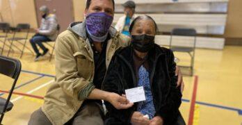 Mujer y hombre usando tapabocas y mostrando una tarjeta de vacunación
