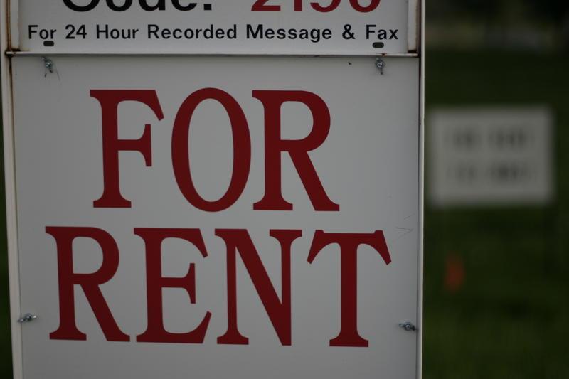 Un signo de alquiler en letras rojas con fondo blanco