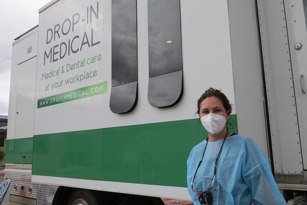 Una mujer posa en frente de una furgoneta