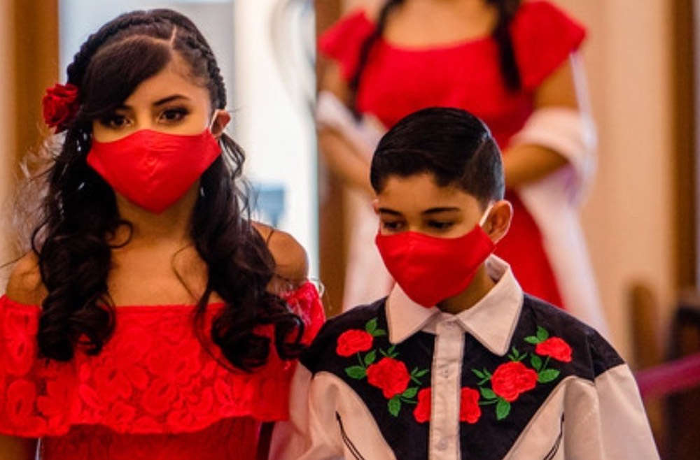 niña y niño con máscaras rojas