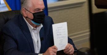 Hombre con mascarilla sosteniendo un papel blanco con las dos manos