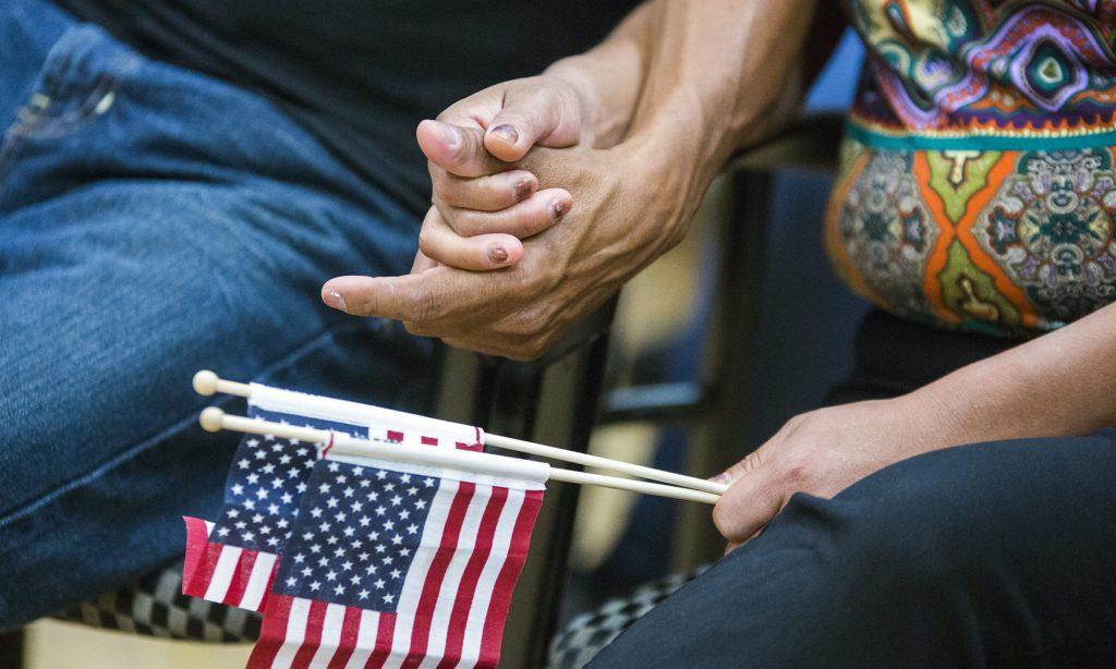 Dos personas tomándose de las manos con una bandera de los Estados Unidos