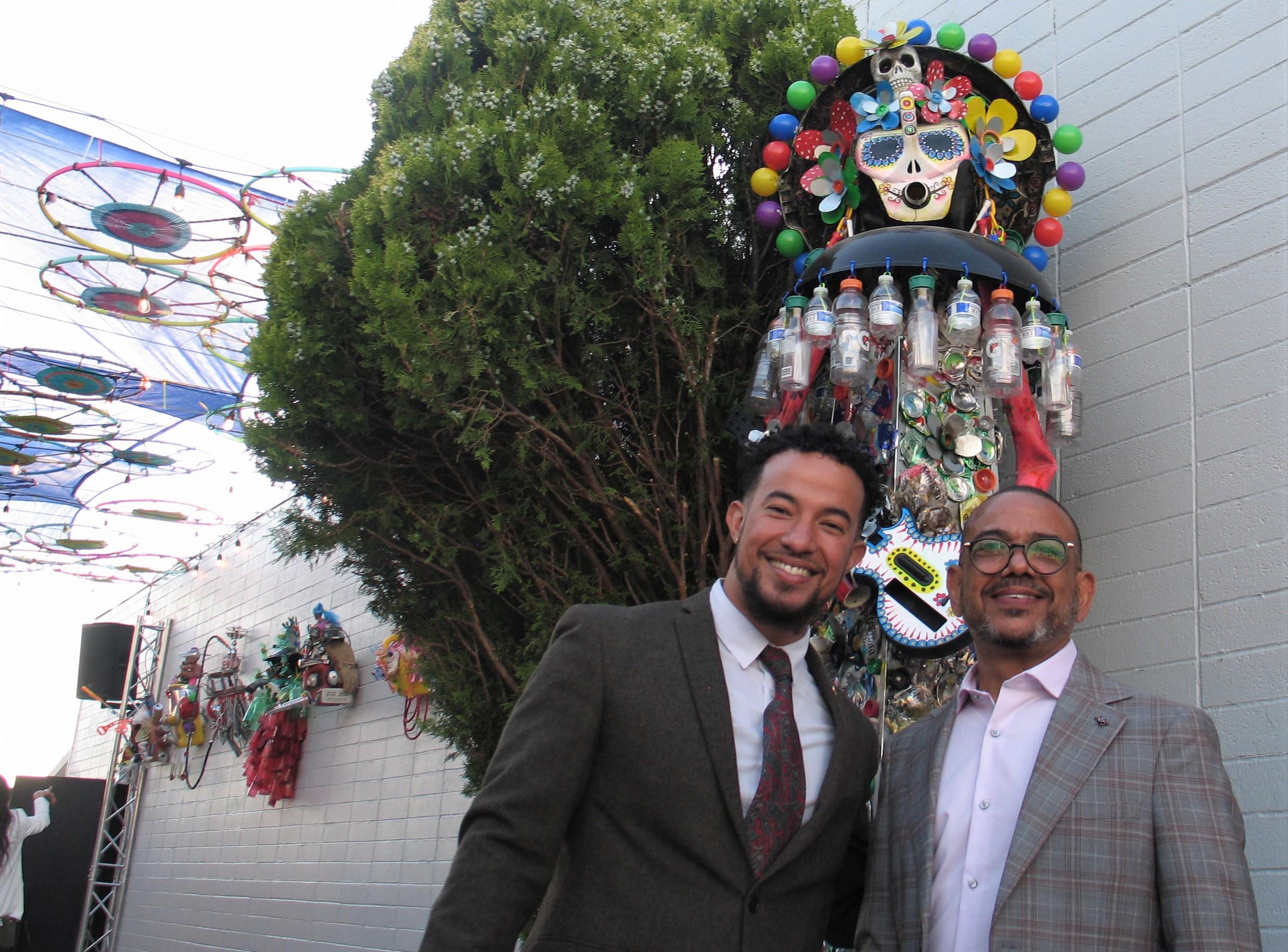 Dos hombres posando con una escultura de reciclaje