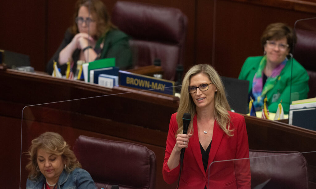 Una mujer rubia con chaqueta roja sosteniendo un microfono