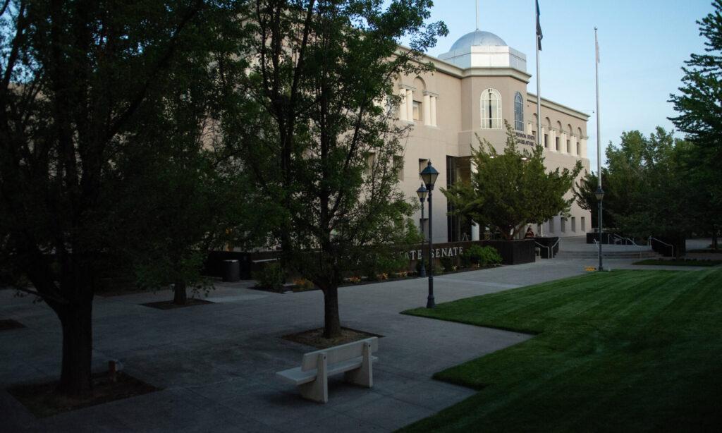 Una banca rodeada de árboles con un edificio blanco detrás