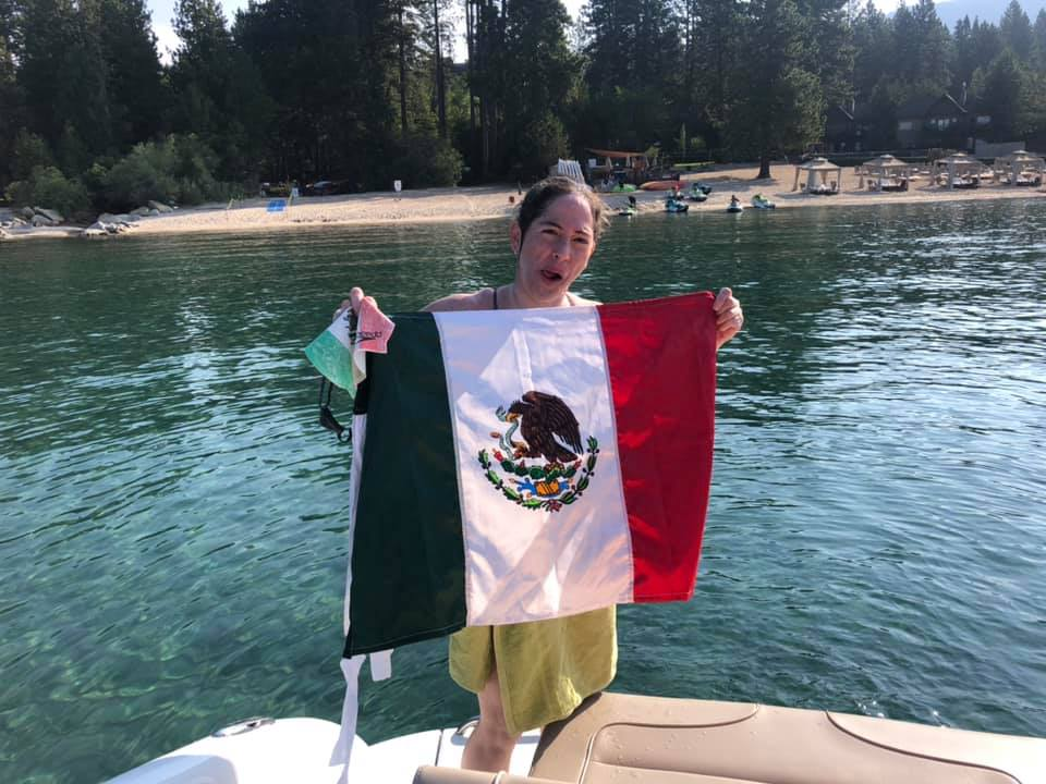 A woman holding a flag at a lake