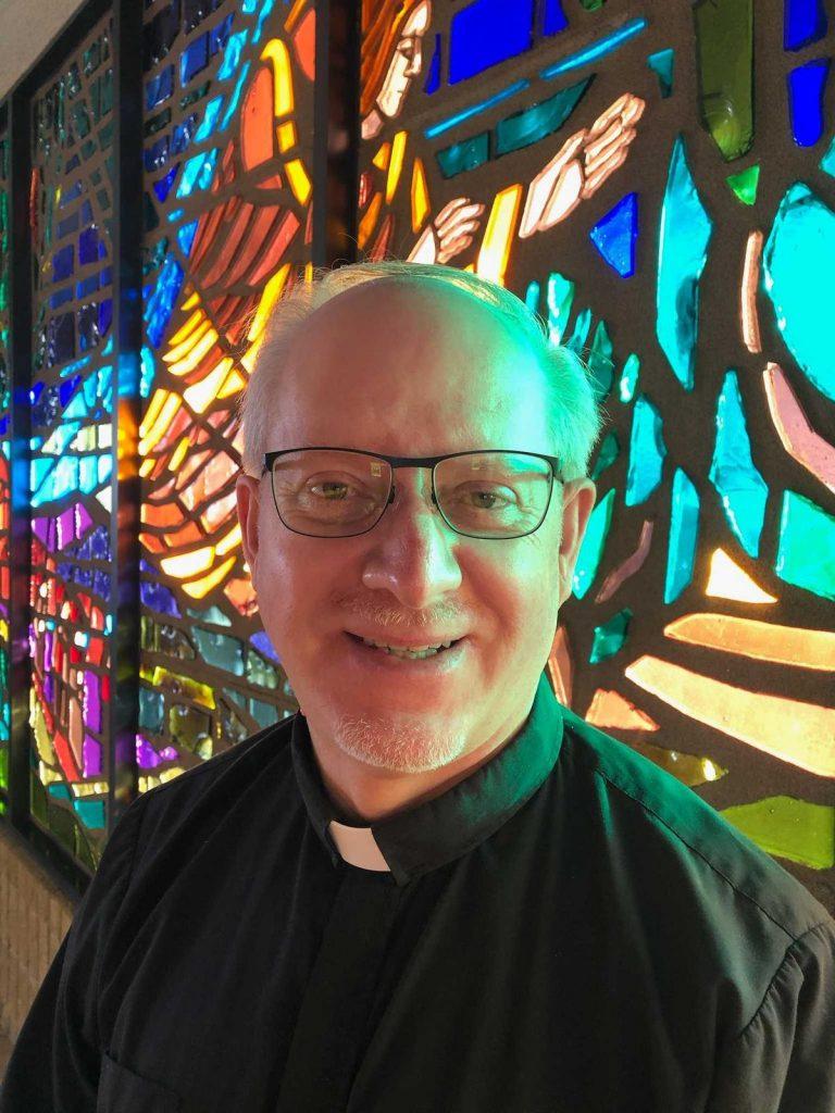 Un hombre que usa gafas y vestidura eclesiástica posa frente a un vitral de iglesia.