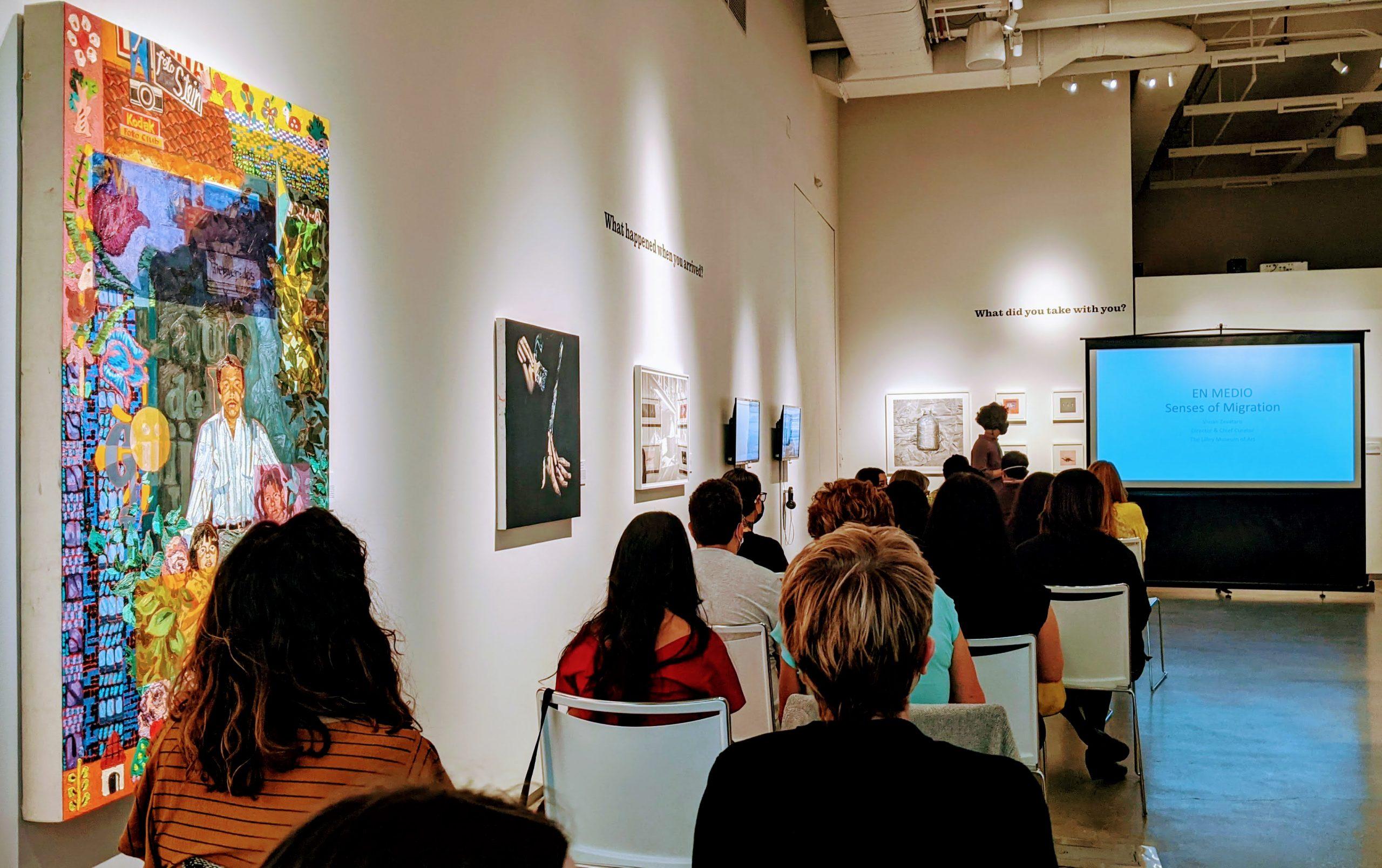 Personas sentadas en un museo escuchan una presentación
