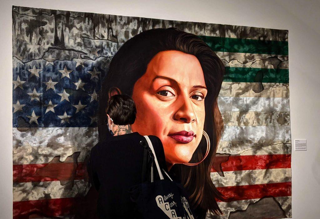 Persona mira de cerca un cuadro con el rostro de una mujer frente a las banderas de Estados Unidos y México