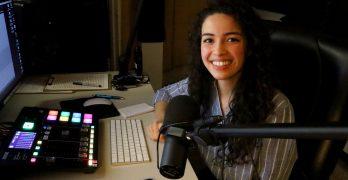 mujer sonriendo sentada en cabina de radio