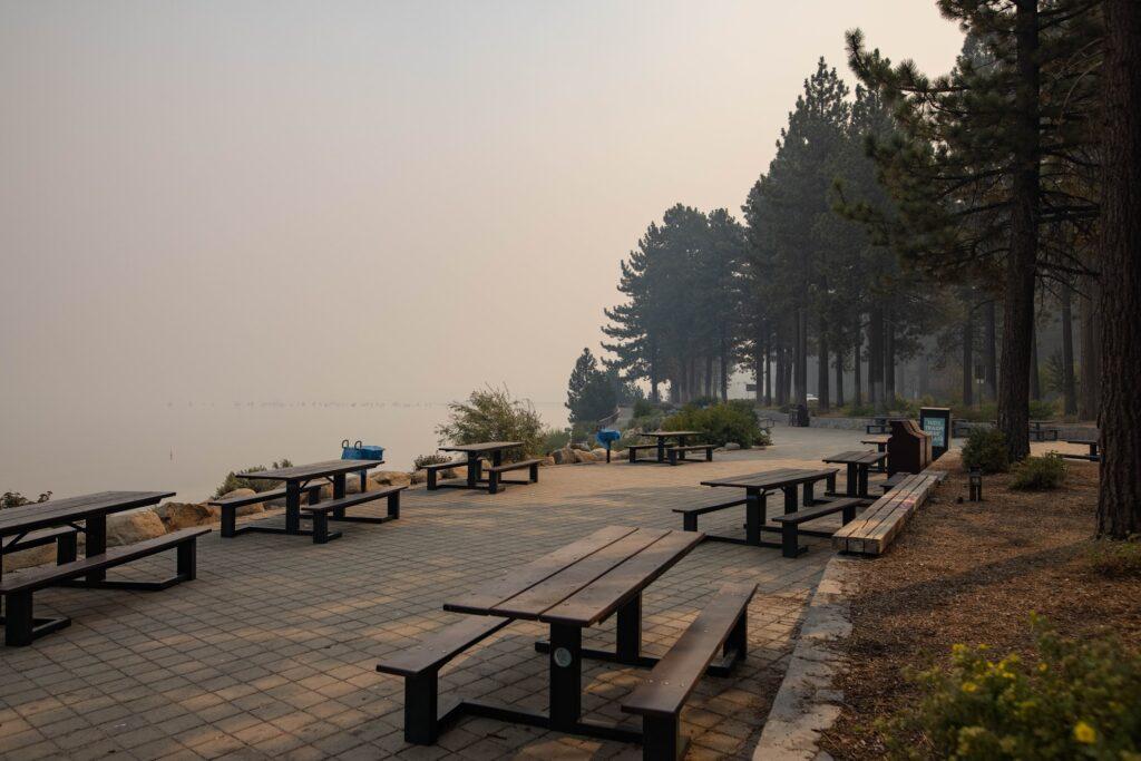 Bancas vacias mirando hacia el lago con humo