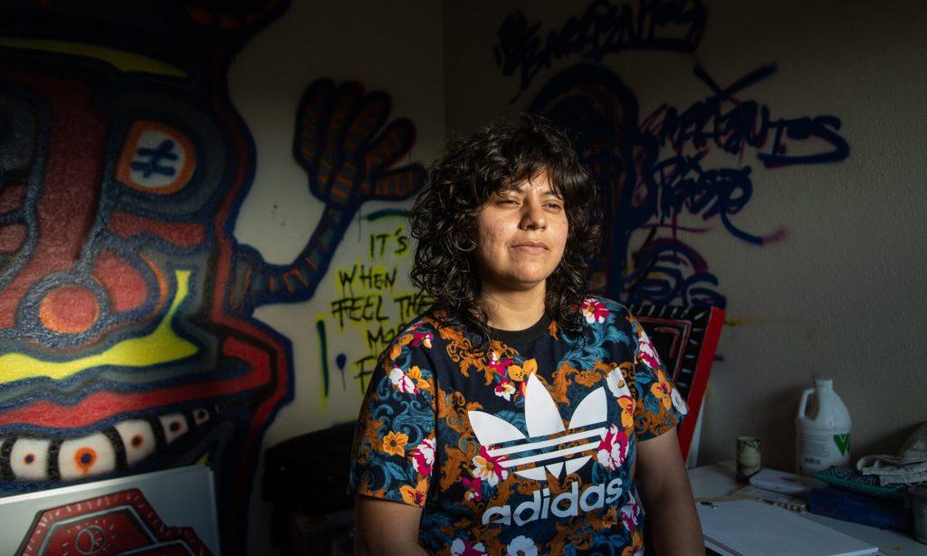 Una mujer posa en frente de un mural pintado