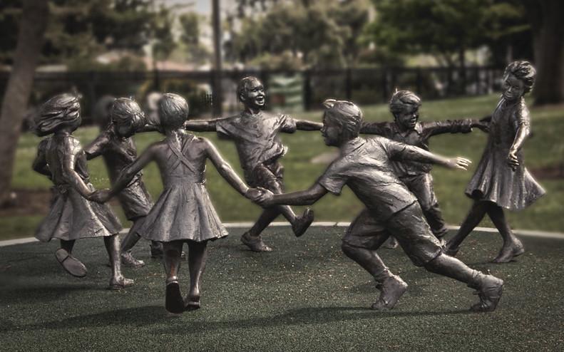foto de la escultura de bronce con siete niños cogidos de la mano en círculo